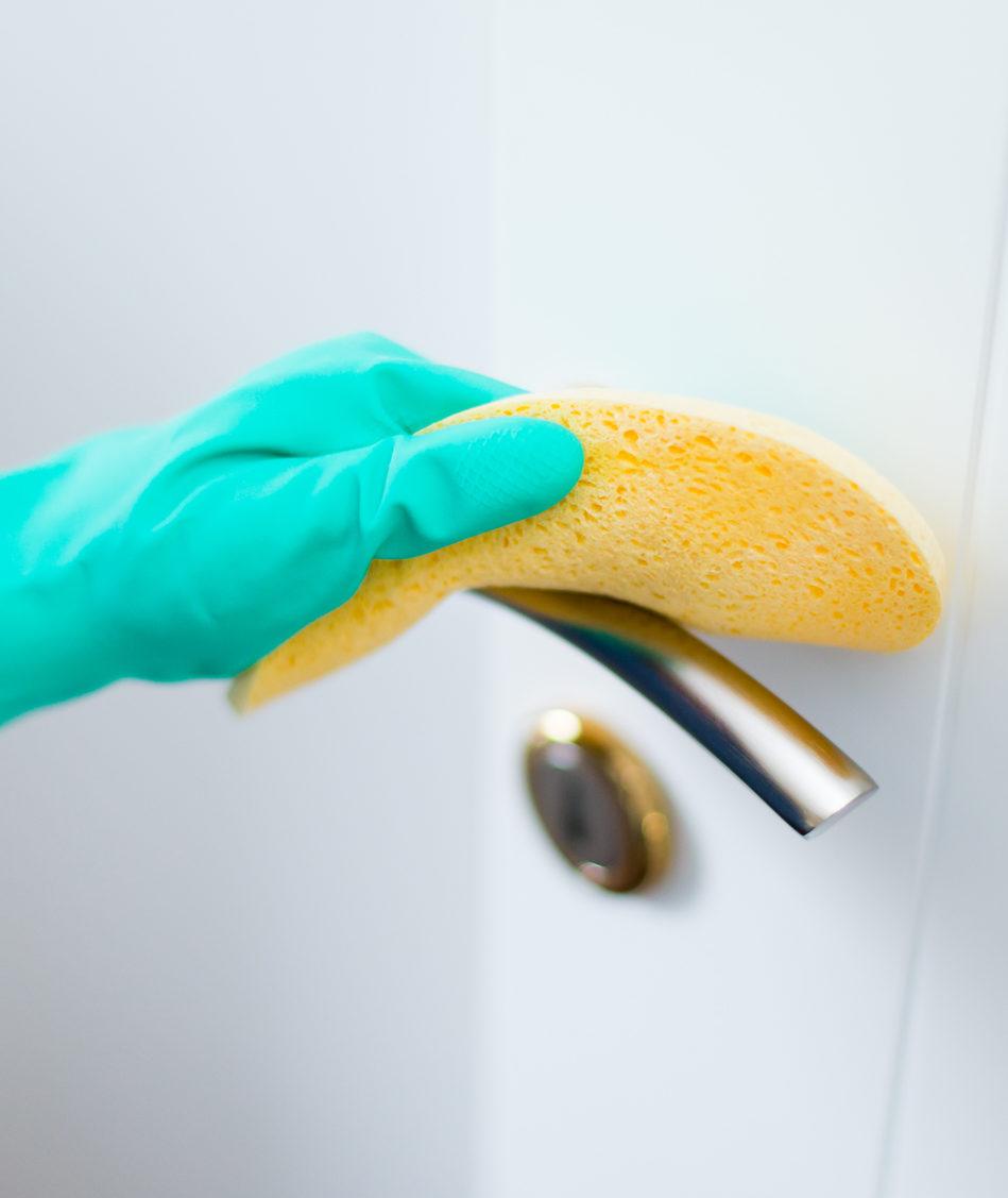 Hand in rubber glove sanitizing a door handle with yellow sponge