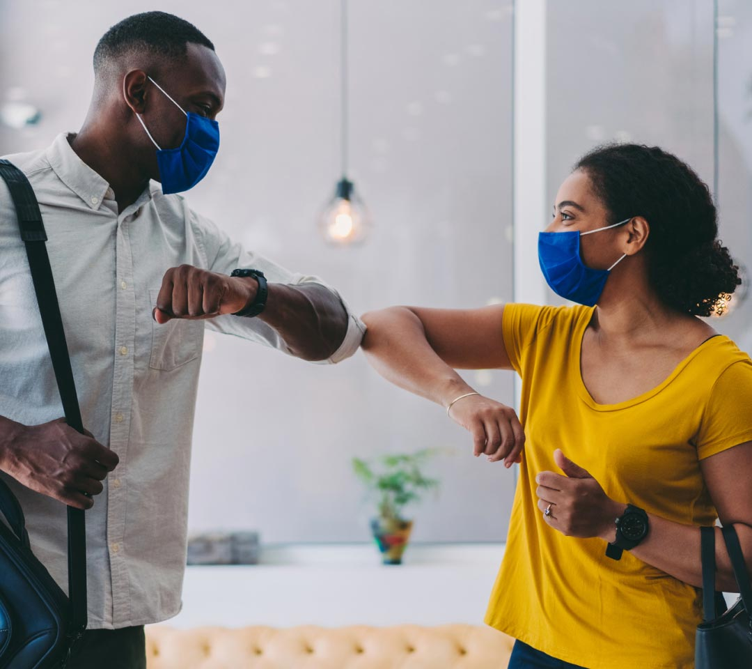 partners elbowing with masks on at the office